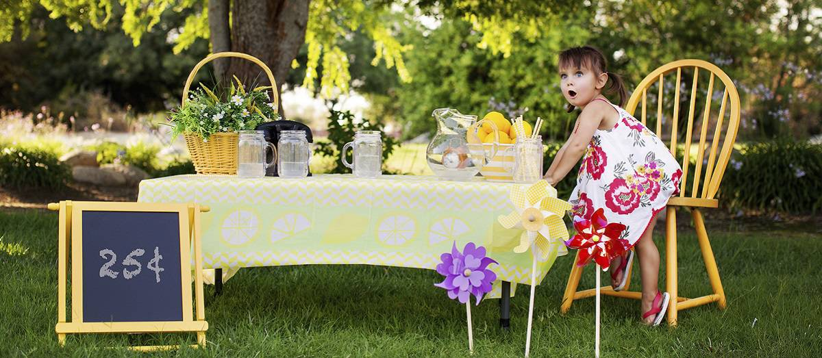 Little Girl at the Lemonade Stand in A Summer Day. She Has a Surprised and Excited Face Expression. She is Happy.